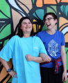 Two young white women laugh standing in front of a colorful mural