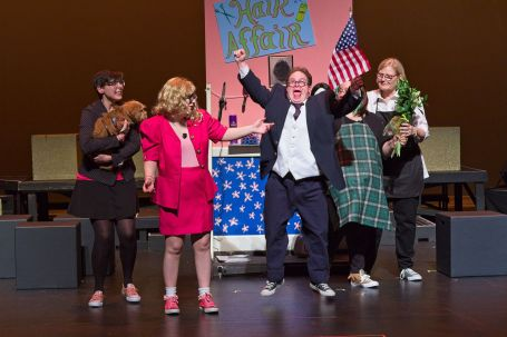 Play performance of Legally Blonde with Actress in pink suit and actor in blue suit waving flag.